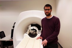 Adam Waytz next to an fMRI scanner in the Social Cognitive & Affective Neuroscience Lab at Harvard University. Photo by Maria Karpenko.