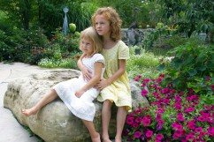 Julia and Zosia on a rock in the garden